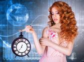 Beautiful woman holding a large clock. — Stock Photo