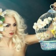Beauty portrait of a girl with a lily in her hair. Blonde holding a cage with a bird — Stock Photo #67657177