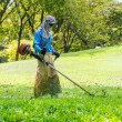 Lawn mower worker man cutting grass in green field park — Foto de Stock   #58509967