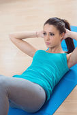 Woman doing abs workout at gym — Stok fotoğraf