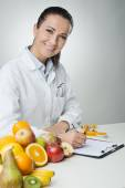 Smiling nutritionist writing medical records — Stock Photo
