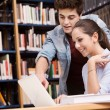 Schoolmates studying together at the library — Stock Photo #63756455