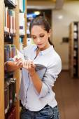 Young woman reading a book at the library — Stock Photo