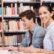 Schoolmates studying together at the library — Stock Photo #65393107