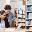 Schoolmates studying together at the library — Stock Photo #65393623