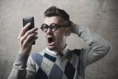 Funny guy having troubles with his phone — Stock Photo