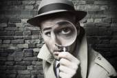 Vintage detective looking through a magnifier — Stock Photo