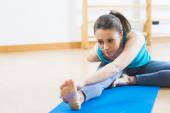 Attractive woman doing stretching exercises at gym — Stock Photo