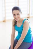 Smiling woman exercising at gym with fitness ball — Stock Photo