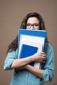 Cute student hiding behind notebooks — Foto de Stock