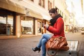 Happy woman sitting on a bench — Stock Photo