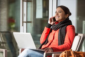 Attractive woman in red coat having a call — Stock Photo
