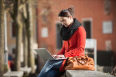 Woman using her laptop in the street — Stock Photo