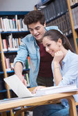 Schoolmates studying together at the library — Stock Photo