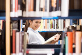 Young student searching for books — Stock Photo