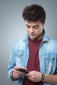 Smiling guy texting with smartphone — Stock fotografie