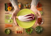 Hands holding red chicory on a dish — Stock Photo
