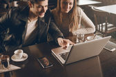 Couple at the bar using a laptop — Stock Photo