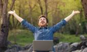 Happy hipster with laptop in the forest — Stock Photo