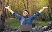 Gelukkig hipster met laptop in het bos — Stockfoto