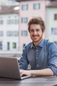 Smiling hipster man using a laptop outdoors — Stock Photo