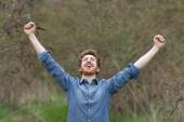 Cheerful hipster with raised fists — Stock Photo