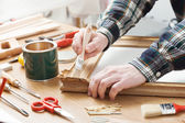 Man varnishing a wooden frame at home — Stock Photo