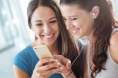 Pretty girls sharing earphones — Stock Photo