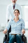 Doctor pushing a patient in wheelchair — Stock Photo