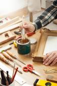 Decorator varnishing a wooden frame — Stock Photo