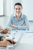 Business team at work and female executive smiling — Stock Photo