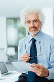 Confident businessman reading paperwork — Stock Photo