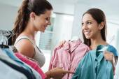 Girl shopping a choosing a shirt at the store — Stock Photo