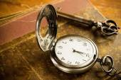 Pocket watch key and old book — Stock Photo