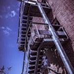 Rusty fire escape of derelict red brick building — Stock Photo #55428321