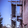 Rusty fire escape of derelict red brick building — Stock Photo #55428383