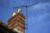 Chimney on a roof with TV aerial and blue sky with light cloud — Stock Photo