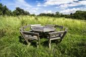 Rustic picnic bench in uncultivated meadow with blue sky — Stock Photo