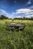 Rustic wooden picnic bench in meadow under blue sky — Stock Photo