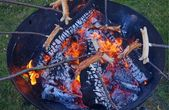 Sausage barbecue and campfire in a fire bowl — Stock Photo