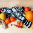 Winter still life with knitted mittens, ginger , orange, pine co — Stock Photo #57336229