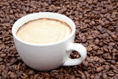 Cup of coffee with cream on a coffee beans background — Stock Photo