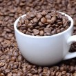 Cup with coffee grains on a coffee beans background — Stock Photo #59433137