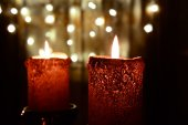 Two orange candles over christmas light — Stock Photo