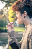 Young girl smoking and relaxing in a park — Stok fotoğraf