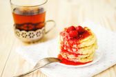 Pancakes with strawberry jam and tea on the wooden table — Stock Photo