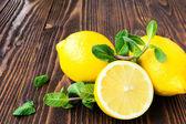 Lemons with mint on wooden table — Foto de Stock