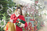 Young woman shows her gift packs inside a Christmas shop — Zdjęcie stockowe