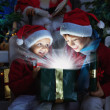 Two children opening Christmas gift — Foto Stock #57455411