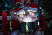 Two children opening Christmas gift — Stock Photo